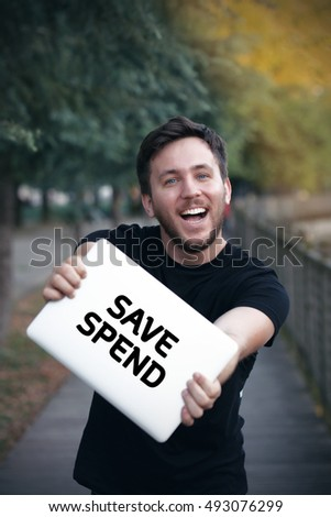 Young man holding Save Spend  sign