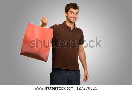 Young Man Holding Shopping Bag Isolated On Grey Background