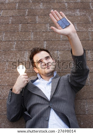 Young man holding small solar unit. - stock photo