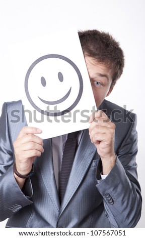 Young man holding smiley face. - stock photo