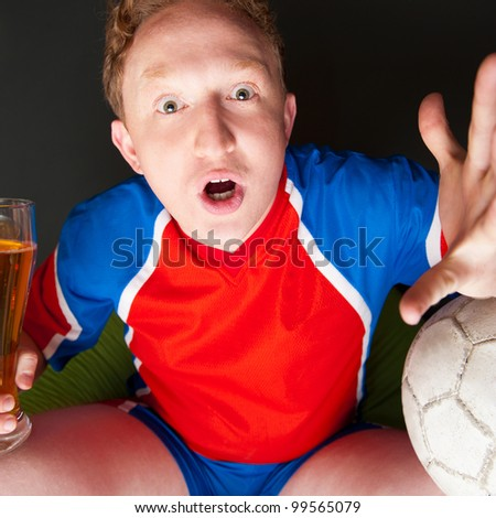Young man holding soccer ball and beer and watching tv translation of game at home wearing sportswear