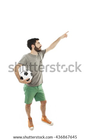 Young man holding soccer ball, pointing. Isolated on white background - stock photo