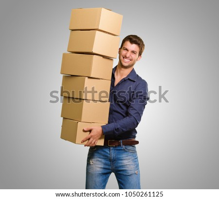 Young Man Holding Stack Of Cardboxes On Grey Background