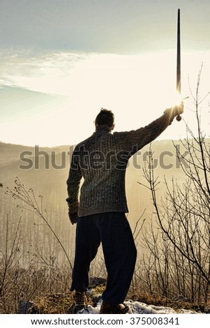 Young man holding sword, Knight stay on the wall with weapon, Sword , Man at sunset holding up sword,  - stock photo