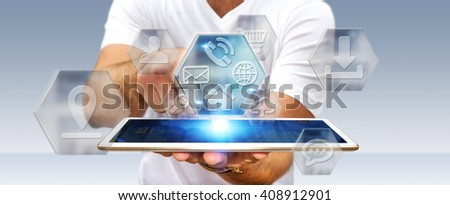Young man holding tablet with application icons interface in his hand - stock photo
