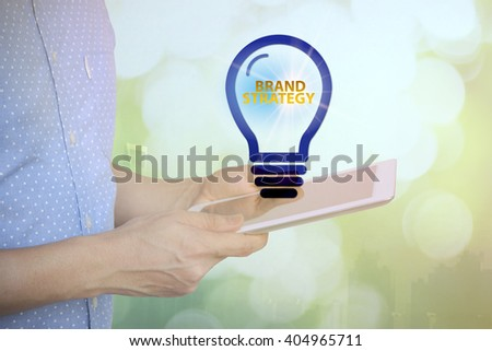 young man holding tablet with BRAND STRATEGY  text on light bulb . soft light with vintage filter. analysis concept , Business concept. Business idea - stock photo