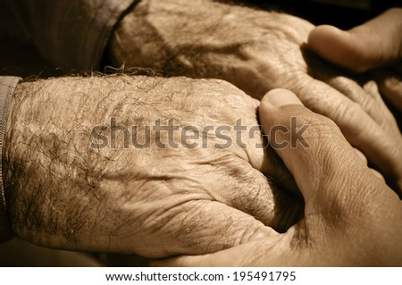 young man holding the hands of an old man - stock photo