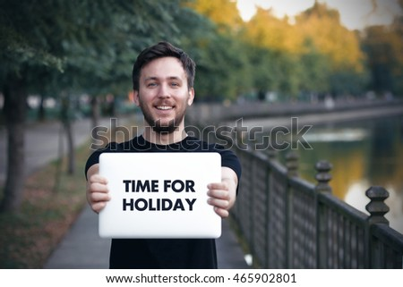 Young man holding  Time For Holiday sign