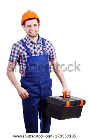 Young man holding toolbox wearing helmet and overalls - stock photo