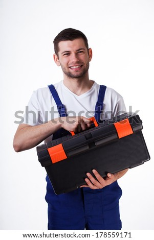 Young man holding toolbox wearing overalls - stock photo