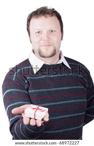 Young man holding valentine gift in his hand. He is giving it somebody. Isolated on white. - stock photo