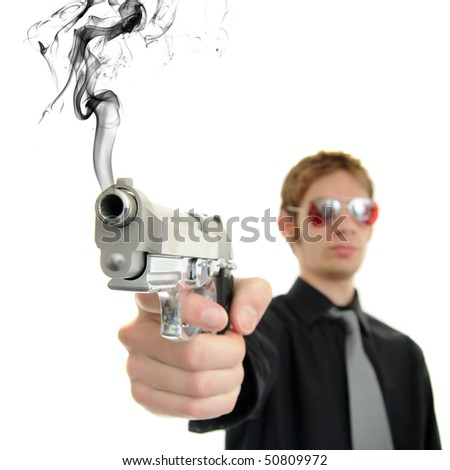 Young man holds his pistol out and shoots out smoke - stock photo
