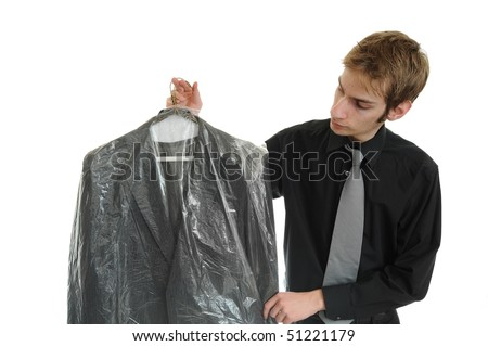 Young man holds newly dry cleaned business jacket coat - stock photo