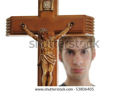 Young man holds up a wooden crucifix of Jesus. Isolated on white. - stock photo