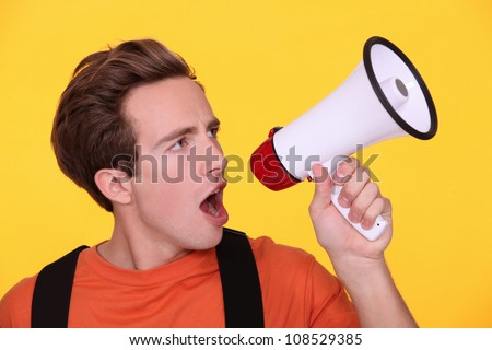 Young man hollering into a megaphone - stock photo