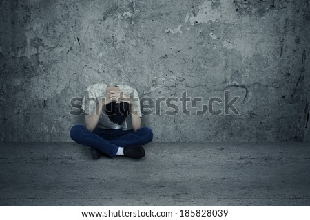 Young man hopeless sitting alone on the floor - stock photo