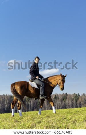 Young man horseriding in the fields by the countryside - stock photo