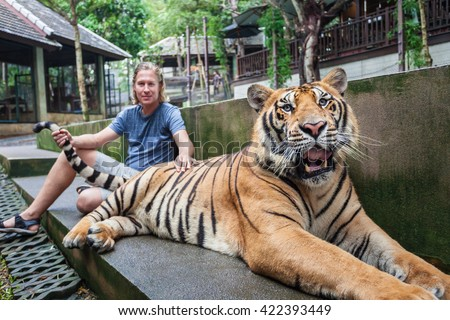 Young man hugging a big tiger in Thailand - stock photo