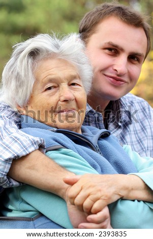 Young man hugs elderly woman. Focus on woman. - stock photo