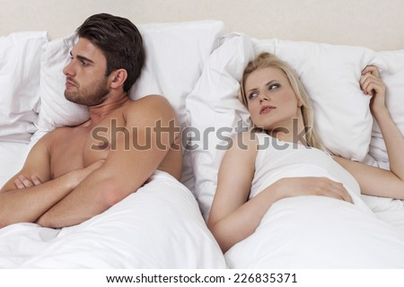 Young man ignoring woman in bed - stock photo