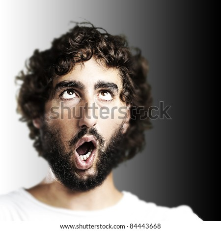 young man imitating a zombie against a black background - stock photo