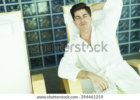 Young man in a bathrobe relaxing in the spa