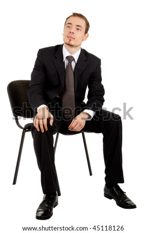 young man in a black business suit sitting on a chair on a white background - stock photo