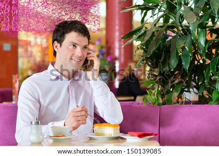Young man in a cafe or ice cream parlor eating a cake and using his phone, maybe he is single or waiting for someone - stock photo