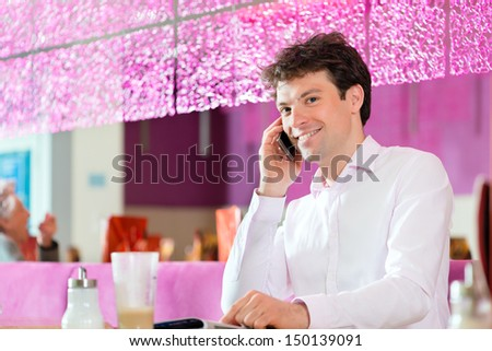 Young man in a cafe or ice cream parlor using his phone, maybe he is single or waiting for someone - stock photo
