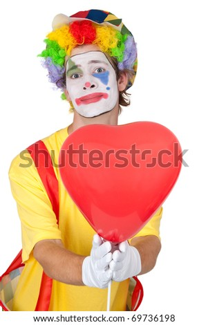 Young man in a clown's costume holding a heart-shaped balloon - isolated - stock photo