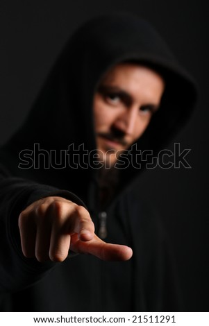 Young man in a dark hood points his index finger towards the camera - stock photo