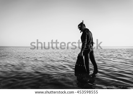 Young man in a diving suit with a mask and flippers goes to the sea in summer outdoor. Monochrome image - stock photo