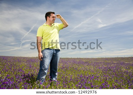 young man in a field looking at the horizon - stock photo