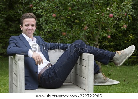 young man in a jacket and jeans sitting outside