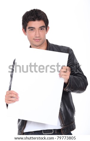 Young man in a leather jacket holding a board left blank for your message - stock photo