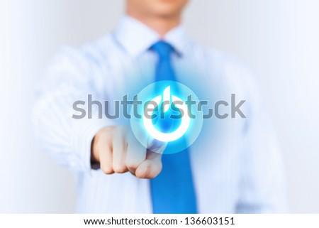Young man in a light shirt and blue tie press the power button. Shallow depth of field. - stock photo