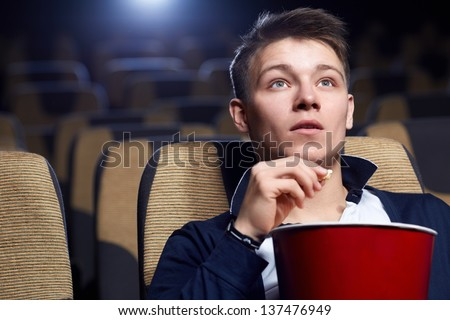 Young man in a movie theater - stock photo