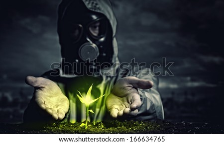 Young man in a protective suit touches to the sprout. post-nuclear future - stock photo