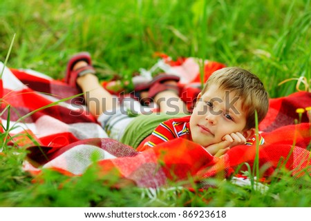 young man in a red shirt lying in the grass on plaid - stock photo