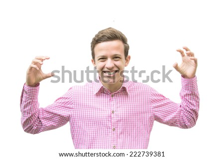 young man in a red shirt smiles and holds up his arms to scare someone - stock photo