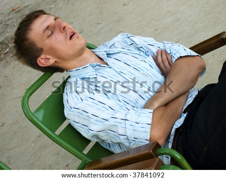 Young man in a shirt sleeping in a chair