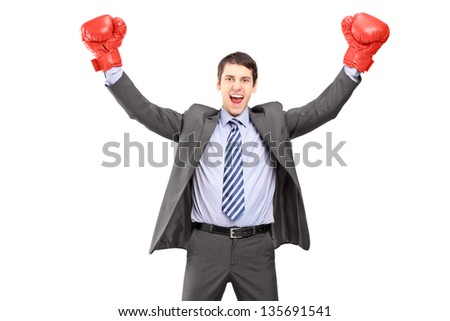 Young man in a suit and boxing gloves, celebrating a win, isolated on white background - stock photo