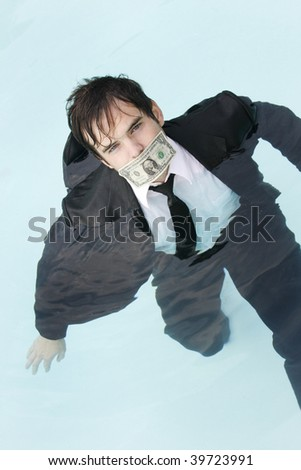Young man in a suit, in the water, with a dollar bill covering his mouth.