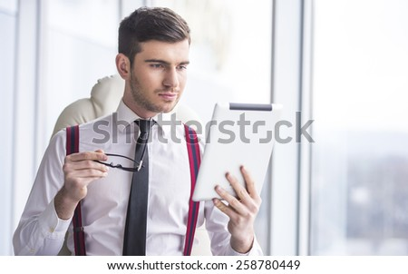 Young man in a suit is holding a tablet before. - stock photo