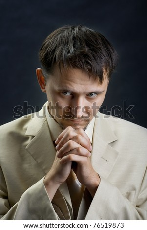 Young man in a suit, praying for something - stock photo