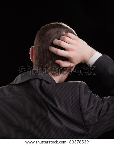 young man in a suit scratching his head in bewilderment
