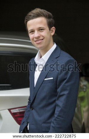 young man in a suit standing outside in front of a car - stock photo