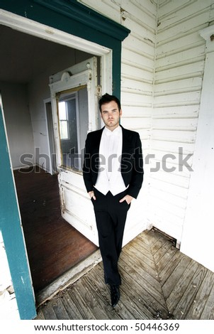 Young man in a tuxedo standing in the doorway of an abandoned house.