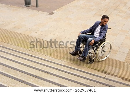 young man in a wheelchair at the bottom of a staircase unable to continue. - stock photo