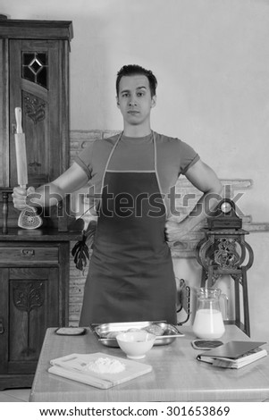 young man in an apron holding rolling pin while standing in kitchen